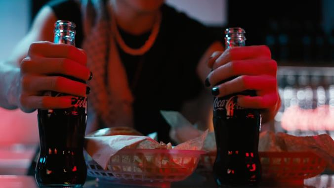 Omar putting two bottles of Coca-Cola on a table.